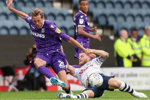 Preston North End's Tom Clarke tackles Stoke City's Peter Crouch