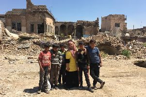 Humeira Bibi with local children in the war-ravaged Iraqi city of Mosul
