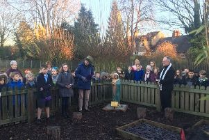 The new statue of Mary in the prayer garden is blessed by Father Michael Sellers in front of the pupils, teachers and governors.