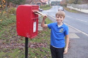 A pupil at St Martin's CofE Primary School posts a letter about unsustainable palm oil production to the Prime Minister Theresa May.