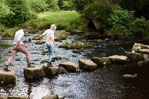 Visitors crossing stepping stones at Hardcastle Crags, West Yorkshire. Hardcastle Crags is a beautiful wooded valley with deep ravines, tumbling streams and glorious waterfalls.