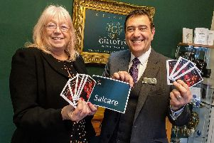 Dena Osborne, head of services at Heanor charity Salcare, left, receives a donation from Anthony Topley, a partner in Gillotts Funeral Directors