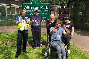 PCSO Louise Richards with students and staff at Alfreton Park School, signing 'How are you?' in Makaton.