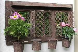 Rustic outdoor garden mirror with four planters.