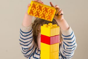 A young child at a nursery playing with large Lego blocks. Picture by PA