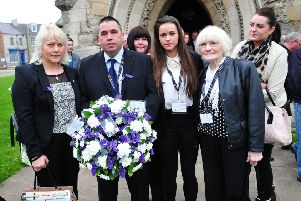 Maria and Trevor Burden (left) with family members hold a wreath in memory of their son Jason.