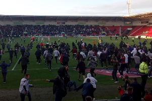 Doncaster Rovers fans invade the pitch after the club secured a place in the play-offs.