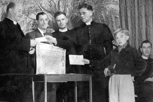 Long service: This picture was taken in 1947 when Canon McMenamin, parish priest of St Joseph's Church, Batley Carr, celebrated 50 years in the priesthood. He is pictured here (left) being presented with a cheque by his curate Fr Cox on behalf of parishioners, and an illuminated address on behalf of the Sisters of the Cross and Passion.