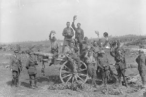 Following the capture of Grevillers by the New Zealand Division, Men of the Royal Garrison Artillery pose beside one of the 4.2 inch guns of a captured battery at Grevillers, 25 August 1918. Note the camouflage netting on the ground, which was designed to prevent the guns from being spotted from the air.  IWM (Q 11243)