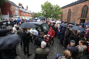 People watch as the coffin of Freddie Starr is driven away following his funeral service at the Prescot Parish Church in Prescot.