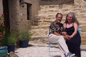 Greg and Sandra sitting outside their Italian farmhouse bed and breakfast.
