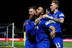 AFC Wimbledon's Scott Wagstaff celebrates scoring his side's third goal of the game against West Ham with team-mate Kwesi Appiah (centre).