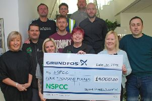 Katy Carmen, front, second right, receives the cheque for �4,000 from members of the Grundfos team, and General Manager Mark Lister, front right