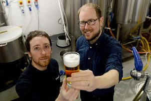 From left, Brewlab project and brewing assistant Julio Romero Johnson examines one of the new beers with Vaux Brewery managing director Steven Smith.
