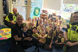 PC Neill Overton, PC Dan Armstrong, police community engagement officer Sally College and community dog Russell with children at Dame Dorothy Primary School