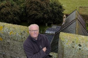 Church warden Keith Usher and the church roof - now protected by tarpaulin.