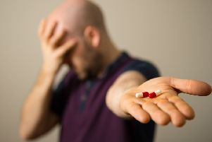 A man holding painkillers.