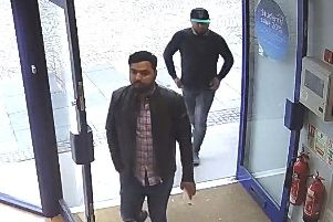 CCTV of two men entering the shop.
