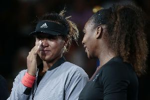 Naomi Osaka, of Japan, wipes a tear as she talks with Serena Williams after Osaka defeated Williams in the women's final of the U.S. Open