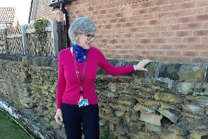Forgotten history: Coun Jo Newing with the centuries old wall outside the Miners' Rest