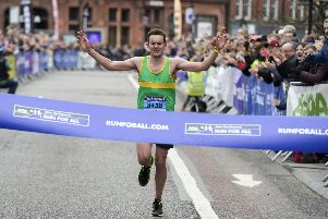Jamie Hall winner of the Sheffield Half Marathon 2019 crosses the line on Pinstone Street
