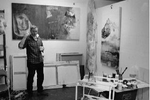 Andy Farr in his studio with two paintings from the exhibition.
