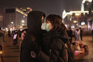 BEIJING, CHINA - JANUARY 22: A Chinese couple wearing their protective masks kiss before saying goodbye to catch a train at Beijing Station before the annual Spring Festival on January 22, 2020 in Beijing, China. The number of cases of a deadly new coronavirus rose to over 400 in mainland China Wednesday as health officials stepped up efforts to contain the spread of the pneumonia-like disease which medicals experts confirmed can be passed from human to human. The number of those who have died from the virus in China climbed to nine on Wednesday and cases have been reported in other countries including the United States,Thailand, Japan, Taiwan and South Korea. (Photo by Kevin Frayer/Getty Images)