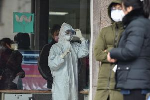 A nurse wearing protective clothing to help stop the spread of a deadly virus which began in the city, looks at a thermometer at the Wuhan Fifth Hospital in Wuhan (Photo by HECTOR RETAMAL/AFP via Getty Images)