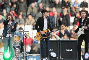 MILTON KEYNES, ENGLAND - FEBRUARY 16: Matthew Bowman (L) of the Pigeon Detectives performs prior to kick off during the FA Cup Fifth Round match between MK Dons and Barnsley at StadiumMK on February 16, 2013 in Milton Keynes, England. (Photo by Ian Walton/Getty Images)
