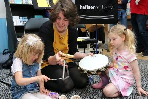Emma Cordwell (left), and her friend Eily St John play with'percussion instruments after the event.
