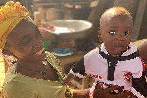 One of the youngsters in Sierra Leone wears one of the donated Morecambe shirts