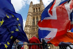 Pro-Brexit and anti-Brexit protesters hold flags as they demonstrate outside the Houses of Parliament in London on March 14, 2019 as members debate a motion on whether to seek a delay to Britain's exit from the EU. - MPs vote on March 14 on whether to seek a Brexit delay, as the chaotic process to end Britain's 46-year membership of the EU plunges the country into deep political crisis. (Photo by Tolga AKMEN / AFP)        (Photo credit should read TOLGA AKMEN/AFP/Getty Images)