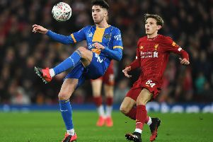 Sean Goss of Shrewsbury Town is challenged by Leighton Clarkson of Liverpool during the FA Cup Fourth Round replay at Anfield