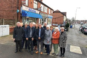 Residents with Coun Lawrence Hunt outside the newsagents which could be converted into a takeaway under plans being considered by Wigan Council