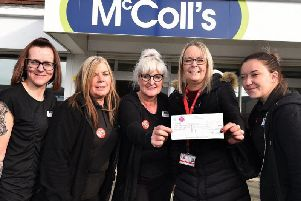 Staff from McColl's presenting the cheque to Harvey's Army