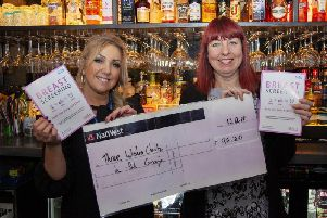 Alison Duncan, owner of Gin on the Lane, (right) presents Janet Ellison, Patient Navigator for the South Lancashire Breast Screening Service, with a donation to the In Pink campaign