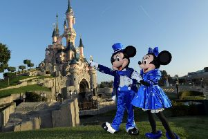 Disney characters Mickey and Mini mouse pose in front of the Sleeping Beauty Castle (BERTRAND GUAY/AFP via Getty Images)