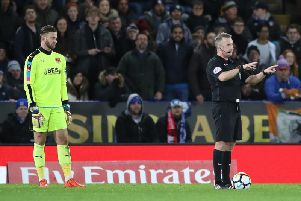 Jon Moss awards Leicester's second goal after consulting VAR.