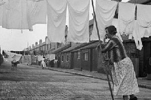 A woman dries her washing in a photograph by Humphrey Spender