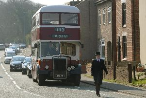 A vintage double decker bus leads the funeral procession along Wigan Road in Standish