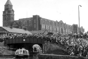It's the mid 80s and hundreds of people await the arrival of the Queen at Wigan Pier to perform the official opening ceremony
