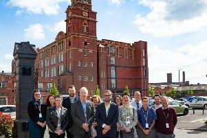 Leader of the council (front row 2nd from left), Councillor David Molyneux, Interact MD (centre, front row), Neil Barber and Wigan Councils director for economy and skills (front row 3rd from right), Becca Heron, outside Trencherfield Mill with Interact employees