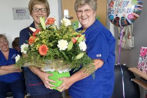 Lorraine Dickinson receiving flowers as she retired after nearly 50 years