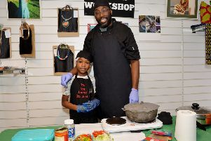 Eight-year-old Mikah Hylton-Mais helps his dad, Richard, at the event at the Westaf African Caribbean shop.