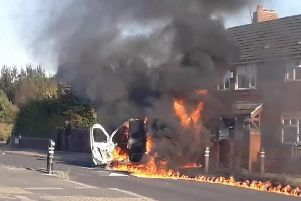 A police van on fire outside homes on Ullswater Crescent in Halton Moor