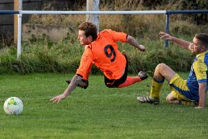 Ryan Barker, of Hall Green United, takes a tumble after being fouled by Swillington's Sean O'Neill. PIC: Steve Riding