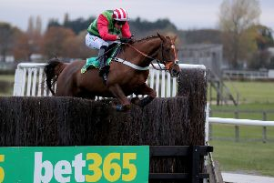 Definitly Red and Danny Cook clear the last in the bet 365 Charlie Hall Chase.