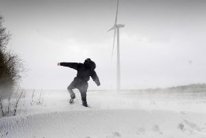 A man walks through snow drifts and blizzard conditions at Hook Moor Wind Farm, near Garforth, Leeds on March 1, 2018. Photo by Simon Hulme