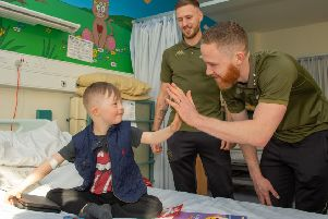 Leeds United stars Barry Douglas and Adam Forshaw make a new friend during the hospital visit.