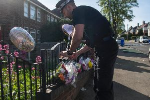Police with the flowers and tributes left in Shiregreen